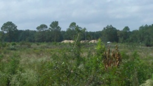 Vehicles on I-10 behind Sabal Trail mound of dirt