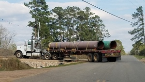 Troy pipe truck turning into Sabal Trail on Knights Ferry Road at McGoggle Road, 30.7484390, -83.4021310