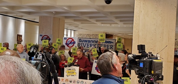 [Suwannee Riverkeeper John S. Quarterman beside banner; Mike Roth of OSFR speaking]
