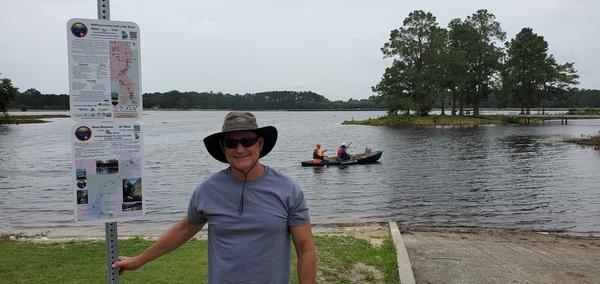 [WLRWT signs, WWALS Trails Committee Chair Dan Phillips, WWALS president Tom H. Johnson Jr. in Suwannee Riverkeeper vessel, Reed Bingham State Park Lake]